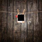 Leeres sofortiges Foto und kleines rotes Papierherz Stockbild