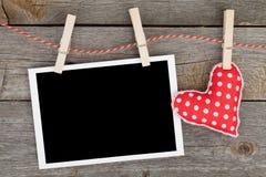 Leeres sofortiges Foto und rotes Herz, die an der Wäscheleine hängt Lizenzfreies Stockfoto