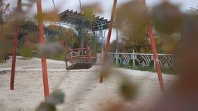 Leeres Spielplatzschwingen, das in Herbstzeit beeinflußt stock video