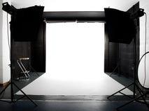 Leeres Studio mit Leuchten und weißem Hintergrund Lizenzfreie Stockbilder