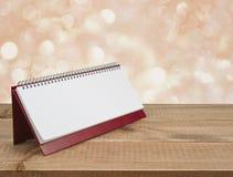 Leeres Tischkalendertagebuch auf Holztisch über abstraktem Hintergrund Lizenzfreie Stockfotos