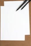 Leeres Weißbuch auf Brown-Hintergrund Lizenzfreies Stockfoto