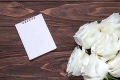 Leeres Weißbuch auf dem Holztisch Ursprüngliche romantische Tapete für den Desktop Weiße Rosen in der rechten Ecke von Lizenzfreies Stockfoto
