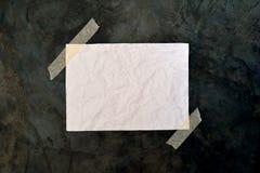 Leeres Weißbuch auf rauer schwarzer Oberfläche Lizenzfreie Stockbilder