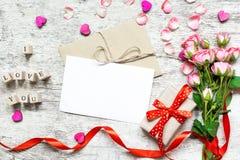 Leeres weißes Grußkartenmodell mit rosa Rosenblumenstrauß Stockbild