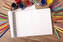 Leeres weißes offenes Buch auf Schulbank mit Bleistiften, Kunst, Handwerksausrüstung Kopieren Sie Platz Stockfoto