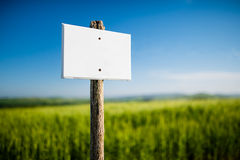 Leeres weißes Schild mit hölzernem Beitrag der Weinlese und schöner Natur im Hintergrund Stockfoto