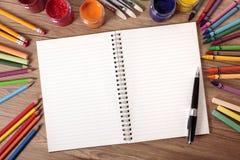 Leeres weißes Schreibensbuch offen auf Schulbank, Stift, Bleistifte, Kopienraum Lizenzfreies Stockfoto