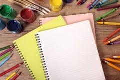 Leeres weißes Schulschreibensbuch, Schulbank, Bleistifte, Kunstversorgungen, Kopienraum Stockfoto