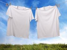 Leeres weißes T-Shirt, das an der Wäscheleine hängt Stockbilder
