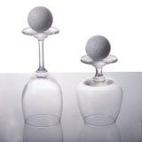 Leeres Weinglas mit Golfball Stockfotos