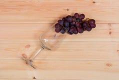 Leeres Weinglas mit roter Traube auf hölzernem Hintergrund Lizenzfreies Stockfoto