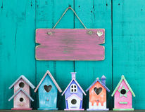 Leeres Zeichen, das am Zaun durch Reihe von Vogelhäusern hängt Stockfoto