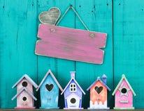 Leeres Zeichen mit dem Herzen, das durch Reihe von Vogelhäusern hängt Stockfotografie