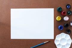 Leeres Zeichenpapier und Farbe auf hölzernem Brett lizenzfreie stockfotos