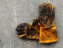 Leerhandschoen na het werk hard op vuile cementgrond stock foto's