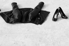 Leerjasje en vrouwelijke zwarte schoenen op asfalt stock foto's