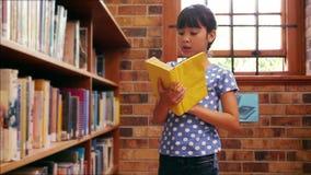 Leerling die boek van plank nemen bij de bibliotheek stock video