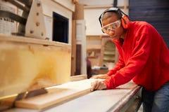 Leerling die Cirkelzaag in Timmerwerkworkshop gebruiken stock afbeelding
