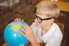 Leerling die een bol van aarde bekijken Royalty-vrije Stock Afbeelding