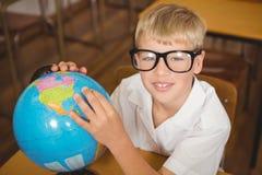 Leerling die een bol van aarde bekijken Stock Afbeelding