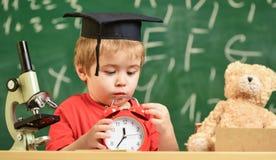 Leerling die op schoolonderbreking wachten Het kind op droevig gezicht bekijkt wekker De jong geitjejongen in academisch GLB dich Royalty-vrije Stock Foto's