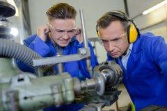 Leerling die oren beschermen tegen lawaaierige machine stock afbeeldingen
