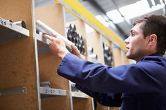 Leerling die Voorraadniveaus in Opslagzaal controleren Royalty-vrije Stock Afbeelding