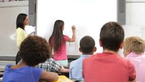 Leerling die zich bij Front Of Class Writing On-Raad bevinden stock videobeelden