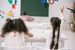 Leerlingen bij bureaus zitten en schoolmeisje die hand opheffen bij les royalty-vrije stock afbeeldingen