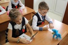 Leerlingen bij een schoolbank bij een les op school - Rusland Moskou de eerste Middelbare school de eerste klasse B - 1 September Stock Afbeeldingen