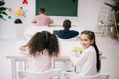 Leerlingen die bij bureaus en leuk schoolmeisje zitten die bij camera in klaslokaal glimlachen royalty-vrije stock foto's