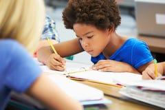 Leerlingen die bij Bureaus in Klaslokaal bestuderen royalty-vrije stock foto's