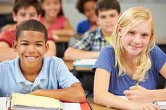 Leerlingen die bij Bureaus in Klaslokaal bestuderen stock foto
