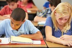Leerlingen die bij Bureaus in Klaslokaal bestuderen stock foto's