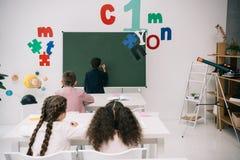 Leerlingen die bij bureaus zitten en klasgenoot het schrijven op bord bekijken stock fotografie