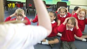 Leerlingen die de Acties van de Leraar kopiëren terwijl het Zingen van Lied stock video