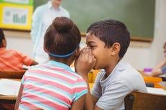 Leerlingen die geheimen fluisteren tijdens klasse Stock Afbeeldingen