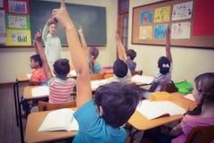 Leerlingen die hun handen opheffen tijdens klasse Stock Foto's
