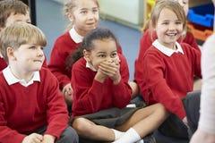 Leerlingen die op Mat Listening To Teacher zitten stock foto's