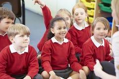 Leerlingen die op Mat Listening To Teacher zitten stock afbeeldingen