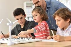 Leerlingen op school met leraar in klasse stock afbeelding