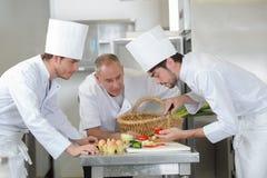 Leerlingschef-kok die tomaat voorbereiden stock fotografie