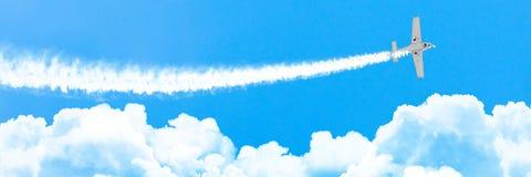 Leerlokflugzeug mit einer Spur der weißen Rauchfliege auf Kumuluswolken im Sommer, Panorama lizenzfreie stockfotos