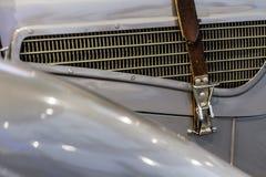 Leerriem op uitstekende oldtimer grijze auto bij de radiatorgrill stock afbeelding