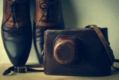 Leerschoenen en een camera in een leergeval Stock Afbeelding
