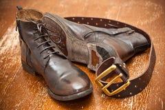 Leerschoenen en een leerriem met gesp. Stock Foto