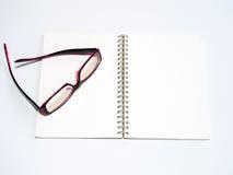 Leerseite eines Notizbuches und der Brillen Stockfotografie
