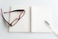 Leerseite eines Notizbuches und der Brillen Lizenzfreies Stockfoto