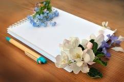 Leerseite eines Notizbuches und des Blumenstraußes der Vergissmeinnichte Lizenzfreie Stockfotografie